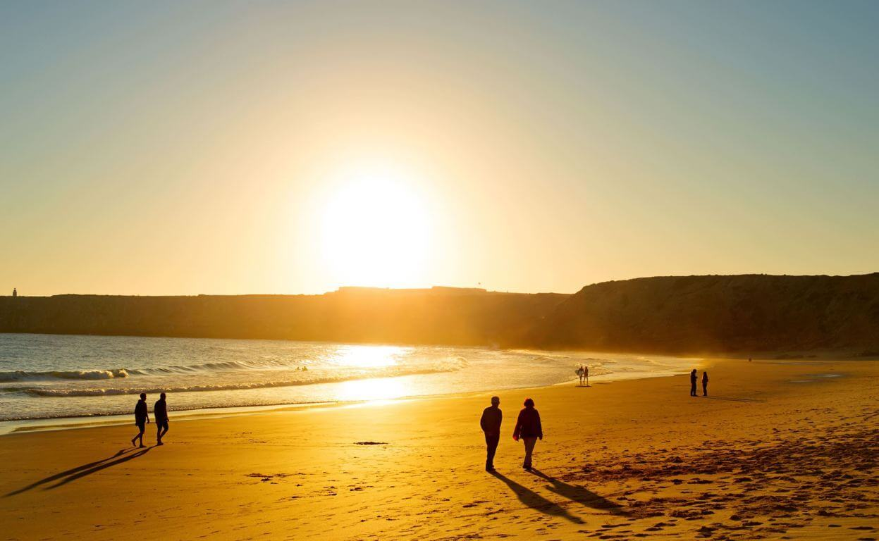 Weather in the Algarve - people walking on a beach in Sagres