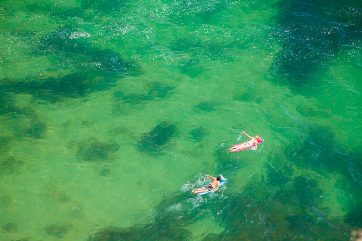 People swimming in crystal clear water near Praia da Corredoura