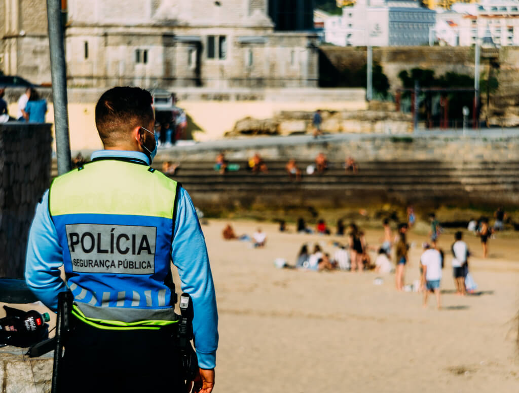 Policeman with face mask on the beach